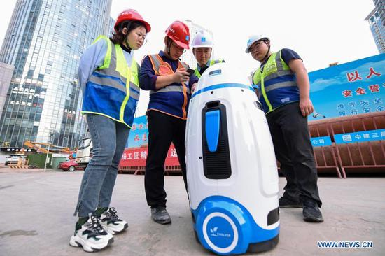 Engineers of the First Company of the China Construction Third Engineering Bureau adjust a smart robot for safety education at a worksite in Nanjing, east China's Jiangsu Province, Nov. 17, 2020. Constructors of the Jinling Zhonghuan construction project have recently adopted a