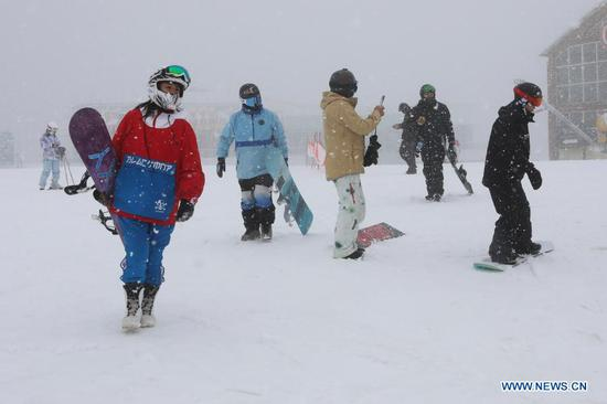 People are going to ski at a ski field during a snowfall in Chongli District of Zhangjiakou City, north China's Hebei Province, Nov. 18, 2020. A snowfall hit Chongli on Wednesday. (Photo by Wu Diansen/Xinhua)