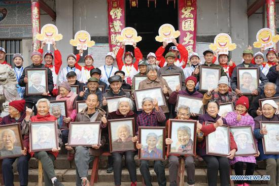Villagers and volunteers pose for a group photo in Xiawei Village of Youlan Town, Nanchang City, east China's Jiangxi Province, Nov. 22, 2020. Since 2014, volunteers from a non-profit organization in Nanchang City have kept on taking photos of smiling faces of farmers aged over 70 years old in nearby villages. The portait photos taken by volunteers were given to farmers for free. By far, the volunteers have taken nearly 4,350 people and 50,000 photos. They aim at collecting high-definition images of 10,000 farmers within 10 years. (Xinhua/Chen Chunyuan)