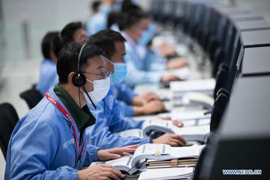 Technical personnel work at the Beijing Aerospace Control Center (BACC) in Beijing, capital of China, Dec. 1, 2020. China's Chang'e-5 spacecraft successfully landed on the near side of the moon late Tuesday and sent back images, the China National Space Administration (CNSA) announced. At 11:11 p.m., the spacecraft landed at the preselected landing area near 51.8 degrees west longitude and 43.1 degrees north latitude, said the CNSA. During the landing process, the cameras aboard the lander took images of the landing area, said the CNSA. (Xinhua/Jin Liwang)
