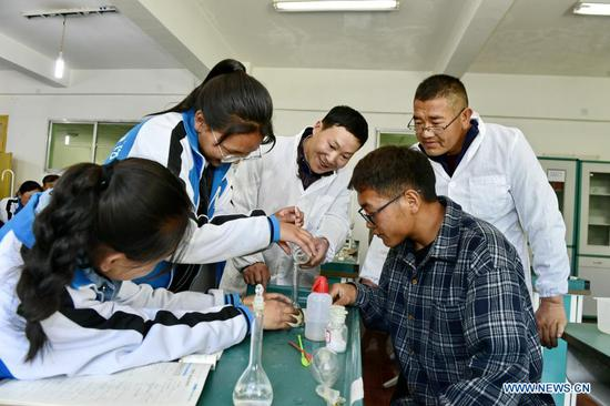 Cai Chunting (C), a teacher from Xiangyang City of central China's Hubei Province, and Cering Choden (back R), a local teacher, tutor students in a chemical experiment in Shannan No.1 Senior High School, southwest China's Tibet Autonomous Region, May 7, 2019. The Chinese government has, so far, spent more than 20 billion yuan on supporting the region's free education program, making education more accessible for nearly nine million students. Students across all grades can also access additional support through a number of projects and initiatives under 40 educational aid projects, providing grants and scholarships, among others. (Xinhua/Zhang Rufeng)