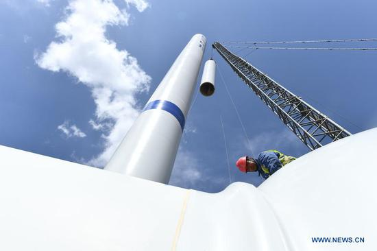 A construction worker builds a 1.3-million-KW wind power plant that is part of a clean energy transmission project linking the Qinghai and Henan provinces in Gonghe County, northwest China's Qinghai Province, June 24, 2020. (Xinhua/Zhang Hongxiang)
