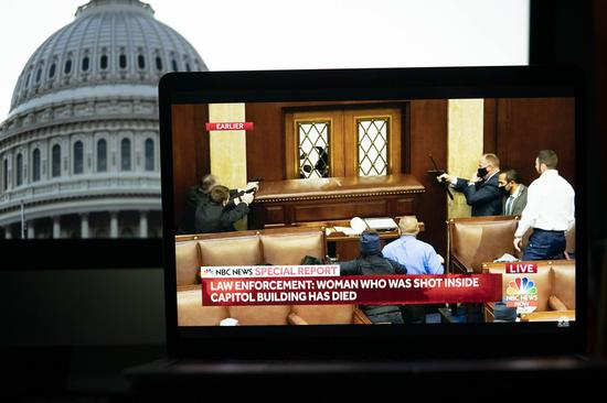 Security staff in the U.S. Capitol building reacting to the chaotic situation in a video feed from NBC news is displayed on a screen in Arlington, Virginia, the United States, on Jan. 6, 2021. (Xinhua/Liu Jie)