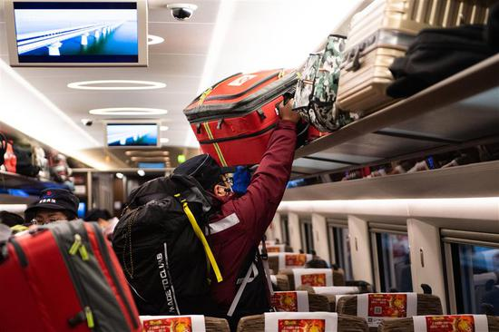 A medic puts away a luggage on a train taking an epidemiological survey team of 23 from central Hunan Province to support the COVID-19 fight in north Hebei Province.