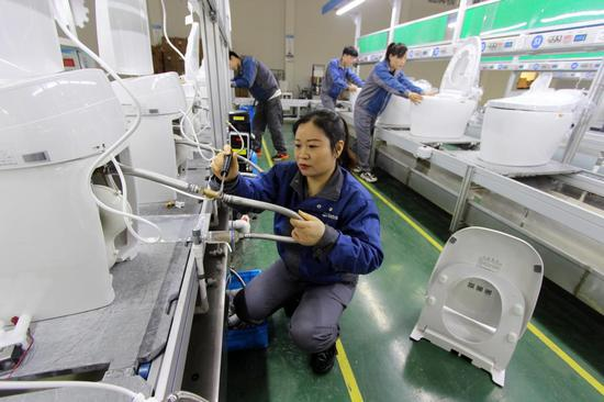 Photo taken on Dec. 11, 2020, shows workers busy assembling and adjusting smart sanitary products in the workshop of a company in Taizhou, east China's Zhejiang province. (People's Daily Online/Jiang Youqing)