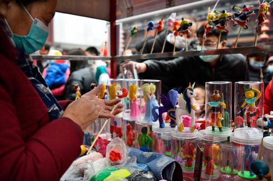 A folk artist makes a clay figurine at an ancient cultural street in Tianjin, north China, Feb. 13, 2021. Many people visited the street on the second day of the Chinese Lunar New Year. (Xinhua/Zhao Zishuo)