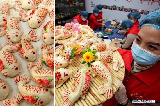 Volunteers make fish-shaped dough snacks symbolizing cornucopia ahead of the Lunar New Year in Zaozhuang, east China's Shandong Province, Feb. 2, 2021. Lunar New Year ranks among the most important festivals in China, and the celebrations are multifaceted, including food. When the Lunar New Year comes, people across China make a variety of snacks which they believe will bring good fortune. (Photo by Sun Zhongzhe/Xinhua)