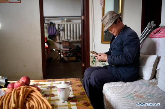 Zhang Junming shops for daily necessities online using smartphone one day before the Chinese Lunar New Year at his new residence at the Binhe Jiayuan relocation site in Yinchuan, northwest China's Ningxia Hui Autonomous Region, Feb. 11, 2021. Zhang Junming, 55, once lived in Hongbaiyang Township, an economic backwater in southern Ningxia. When he was young, Zhang had been severely injured in an accident, and hence suffered from leg disabilities that prevented him from seeking job opportunities in the big cities. So he and his family had to scrape a living out of poor yields on the barren farmland. The quality of life was exacerbated by lack of drinking water and poor traffic condition. Such difficult scenario came to a turning point in 2013, when the Zhang family moved out of Hongbaiyang under a government-backed ecological poverty-relief relocation scheme. The relocation site they moved into has paved roads, sound infrastructure and a slew of support policies, which rekindled Zhang's hope for the future. Eight years since the relocation, huge changes have taken place in the life of the Zhang family. At present, Zhang's two sons work in the regional capital Yinchuan, whereas his daughter-in-law is employed in a textile factory nearby. Meanwhile, both Zhang and his wife earn from job posts with social sponsorship. (Xinhua/Wang Peng)