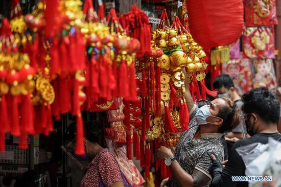 A man arranges decorations at Chinatown in Manila, the Philippines on Feb. 11, 2021. The year 2021 is the Year of the Ox according to the Chinese zodiac. With Chinese culture and food becoming increasingly popular, people not only in China, but all over the world also take part in the Chinese New Year celebrations. (Xinhua/Rouelle Umali)