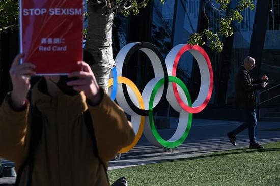A lone protester (L) holds up a sign in reference to recent comments made by Tokyo Olympics chief Yoshiro Mori, next to a display of the Olympic Rings outside the Japan Olympic Museum in Tokyo on February 11, 2021.