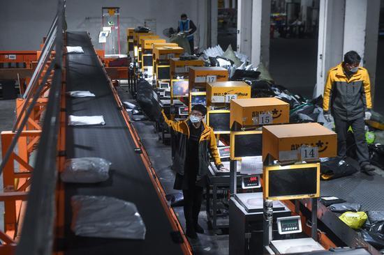Staff workers work at a warehouse of courier service provider Yunda Express in Zhili Town of Huzhou, east China's Zhejiang Province, Feb. 8, 2021. (Xinhua/Xu Yu)