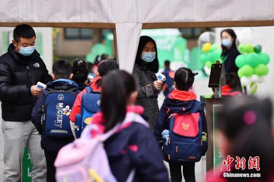 Students receive temperature checking when entering a primary school in Beijing, capital of China, March 1, 2021. Primary and middle schools in Bejing started the new semester on Monday. (Photo/China News Service)