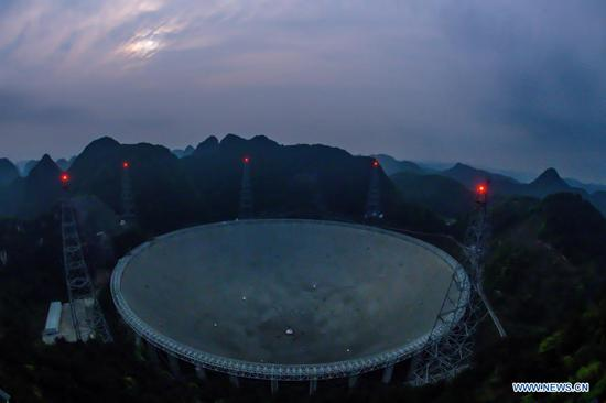 Photo taken on March 28, 2021 shows China's Five-hundred-meter Aperture Spherical radio Telescope (FAST) under maintenance in southwest China's Guizhou Province. FAST has identified over 300 pulsars so far. Located in a naturally deep and round karst depression in southwest China's Guizhou Province, it officially began operating on Jan. 11, 2020. (Xinhua/Ou Dongqu)