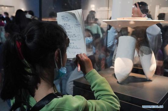 A pupil observes an exhibit at the Sanxingdui Museum in Guanghan City, southwest China's Sichuan Province on April 3, 2021. The major discoveries made recently by archaeologists at the legendary Sanxingdui Ruins site in Sichuan have triggered wide interest among the general public in China, and many of them chose to visit the Sanxingdui Museum during the three-day Qingming holiday. (Xinhua/Liu Mengqi)