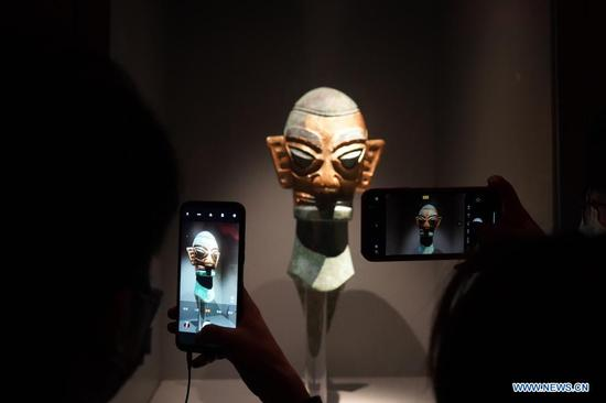 People take a photo of an exhibit at the Sanxingdui Museum in Guanghan City, southwest China's Sichuan Province on April 3, 2021. The major discoveries made recently by archaeologists at the legendary Sanxingdui Ruins site in Sichuan have triggered wide interest among the general public in China, and many of them chose to visit the Sanxingdui Museum during the three-day Qingming holiday. (Xinhua/Liu Mengqi)