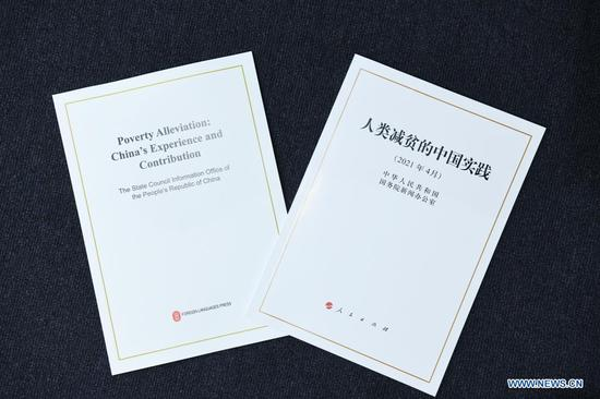 "Photo taken on April 6, 2021 shows the Chinese and English editions of the white paper titled ""Poverty Alleviation: China's Experience and Contribution"" issued by the State Council Information Office in Beijing, capital of China. The white paper was issued to record the course of the Chinese people's great fight in eliminating extreme poverty, introduce China's approach, and share its experience and actions in poverty alleviation. (Xinhua/Jin Liangkuai)"