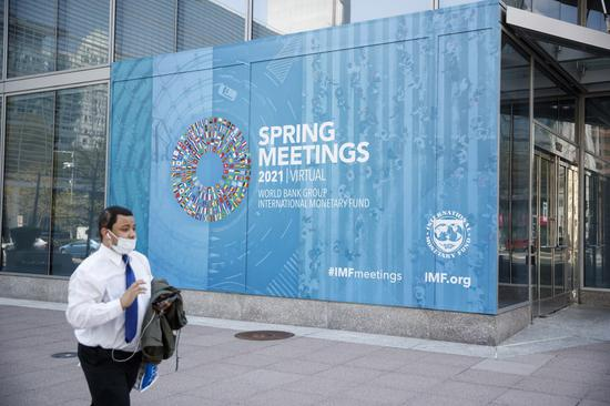 A man walks past the International Monetary Fund headquarters in Washington, D.C., the United States, on April 6, 2021. (Photo by Ting Shen/Xinhua)