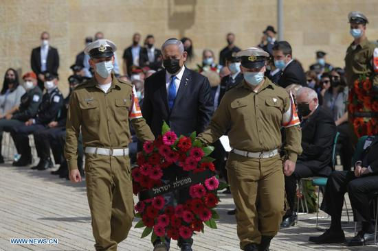 Israeli Prime Minister Benjamin Netanyahu (C) attends an official wreath-laying ceremony marking the annual Holocaust Remembrance Day at Yad Vashem in Jerusalem, on April 8, 2021. (Alex Kolomoisky/JINI via Xinhua)