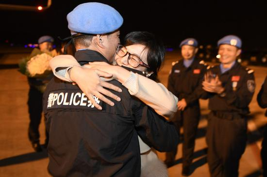A Chinese peacekeeper hugs his wife upon his arrival at the Hangzhou Xiaoshan International Airport in Hangzhou, capital of east China's Zhejiang Province, Feb. 27, 2018, after conducting a one-year mission in South Sudan. The sixth team of Chinese peacekeeping police to South Sudan, with seven members all selected from Zhejiang, arrived in Hangzhou that evening. (Xinhua/Huang Zongzhi)