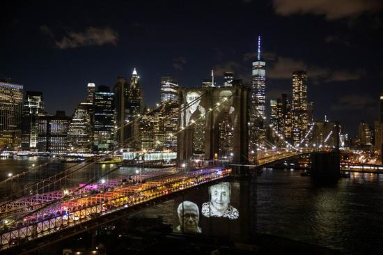 Images of New Yorkers lost to the COVID-19 pandemic are projected onto the Brooklyn Bridge in New York, the United States, March 14, 2021. (Xinhua/Michael Nagle)