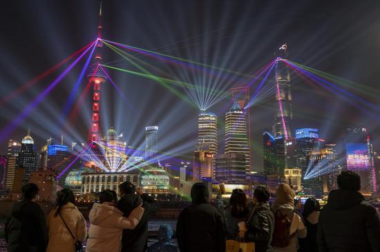 People enjoy the light show at the Bund in east China's Shanghai, Jan. 2, 2021. (Xinhua/Wang Xiang)