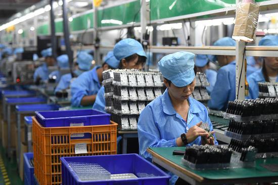 Workers make walkie-talkies at an electronics company in Xiamei Township, Nan'an, southeast China's Fujian Province, Aug. 26, 2020. (Xinhua/Song Weiwei)