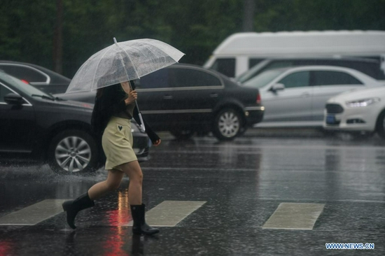 A citizen walks in rain near a subway station in Beijing, capital of China, July 12, 2021. Heavy rainstorm has lashed the Chinese capital Beijing since 6 p.m. Sunday with precipitation up to 116.4 mm, according to the municipal flood control department. From 6 p.m. Sunday to 9 a.m. Monday, Beijing registered average rainfall of 65.9 mm. Urban areas of the city reported higher average precipitation of 79.9 mm. (Xinhua/Peng Ziyang)