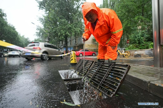 A worker checks the drainage system on a road in Chaoyang District of Beijing, capital of China, July 12, 2021. Heavy rainstorm has lashed the Chinese capital Beijing since 6 p.m. Sunday with precipitation up to 116.4 mm, according to the municipal flood control department. From 6 p.m. Sunday to 9 a.m. Monday, Beijing registered average rainfall of 65.9 mm. Urban areas of the city reported higher average precipitation of 79.9 mm. (Xinhua/Ju Huanzong)