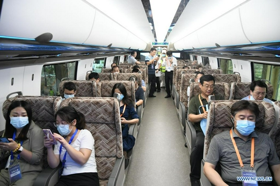 Visitors experience for themselves inside a cabinet of China's new high-speed maglev train in Qingdao, east China's Shandong Province, July 20, 2021. China's new high-speed maglev train rolled off the production line on Tuesday. It has a designed top speed of 600 km per hour -- currently the fastest ground vehicle available globally. The new maglev transportation system made its public debut in the coastal city of Qingdao, east China's Shandong Province. It has been self-developed by China, marking the country's latest scientific and technological achievement in the field of rail transit, according to the China Railway Rolling Stock Corporation. (Xinhua/Li Ziheng)