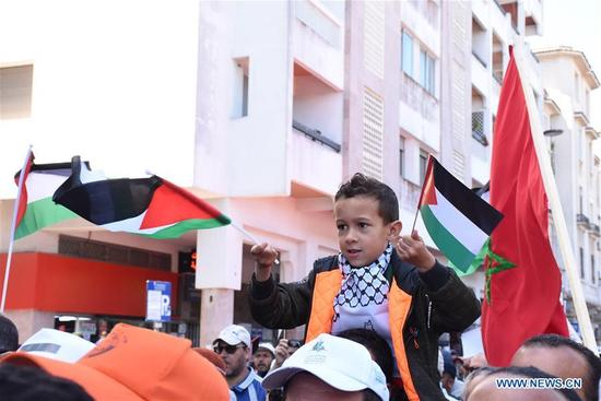 A boy waves a Palestinian flag in a march to commemorate the upcoming Nakba Day in Rabat, Morocco, on May 13, 2018. Thousands of people marched Sunday here to commemorate the upcoming Nakba Day, or