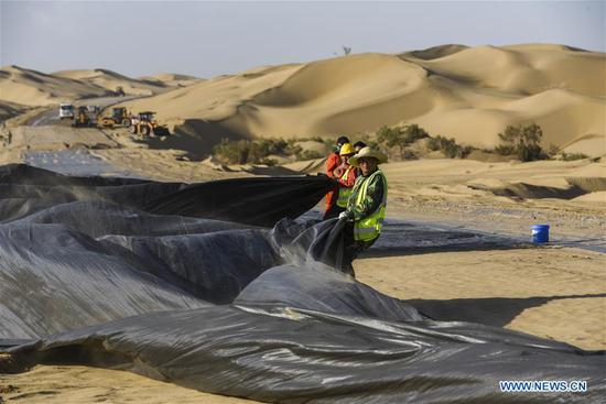 Staff members work at a desert road construction site in Taklimakan desert in northwest China's Xinjiang Uygur Autonomous Region, July 5, 2018. An over 300-km-long desert road, linking Xinjiang's Yuli County to remote Qiemo County, is now under construction. It's the third that-kind-of road crossing China's largest desert Taklimakan nicknamed