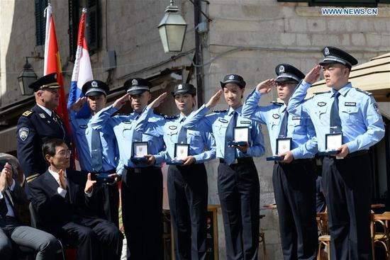 Zeljko Prsa, Deputy General Police Director of Croatia, gives police badges to Chinese police officers during the launching ceremony of joint police patrol between China and Croatia in Dubrovnik, Croatia, on July 15, 2018. Six uniformed Chinese police officers started joint patrol with their Croatian counterparts here on Sunday. (Xinhua/Gao Lei)