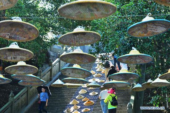 Tourists walk on stone steps decorated with bamboo rain hats at Yushilin scenic spot in Hezhou City, south China's Guangxi Zhuang Autonomous Region, Oct. 5, 2018. (Xinhua/Huang Xuhu)