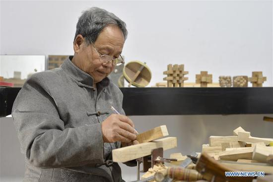Hou Quanchen designs a Kong Ming Lock in Shahe City, north China's Hebei Province on Nov. 28, 2018. Hou Quanchen, who is in his seventies, has devoted himself in the studying and making of Kong Ming Locks and has tried to promote this art among local residents ever since his retirement. (Xinhua/Tian Xiaoli)