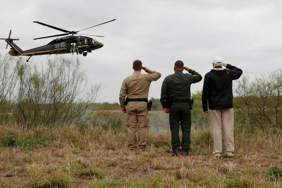 President Donald Trump salutes a U.S. Border Patrol helicopter with U.S. Border Patrol agents as it flies over the Rio Grande River during his visit to the U.S. - Mexico border in Mission, Texas, U.S., January 10, 2019. REUTERS/Leah Millis
