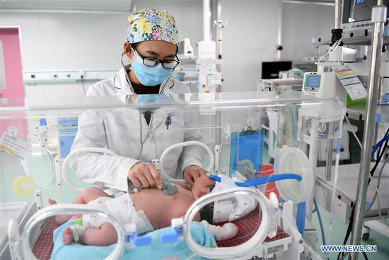 A nurse checks the physical condition of a baby at an intensive care unit in a care center for mothers and children in Suixian County, central China's Henan Province, Feb. 4, 2019. People from various industries stick to their posts on the eve of the Spring Festival which falls on Feb. 5 this year. (Xinhua/Liu Junxi)