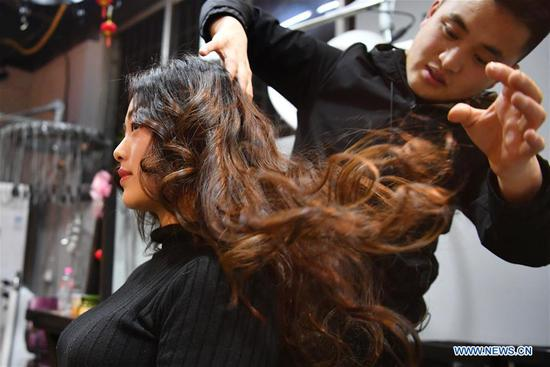 A woman has her hair done at a barber shop in Tianshui, northwest China's Gansu Province, March 5, 2019. Along with China's reform and opening-up starting from 1978, Chinese women have refreshed their images year after year, which can be simply seen from their hairstyles. Women's hairstyles, just like a mirror, reflect fashion changes and most importantly, Chinese women's increasingly diversified definition of beauty. (Xinhua/Chen Bin)