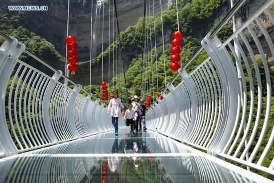 Tourists walk on a glass bridge at a scenic spot in Zigui County, Yichang, central China's Hubei Province, May 2, 2019. (Xinhua/Wang Gang)