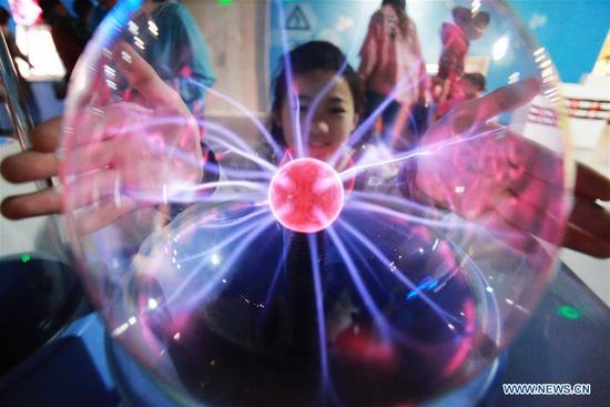 A child tries the plasma magic ball at Yangzhou Science & Technology Museum in Yangzhou, east China's Jiangsu Province, May 3, 2019. People learn knowledge in various museums during the Labor Day holiday. (Xinhua/Meng Delong)