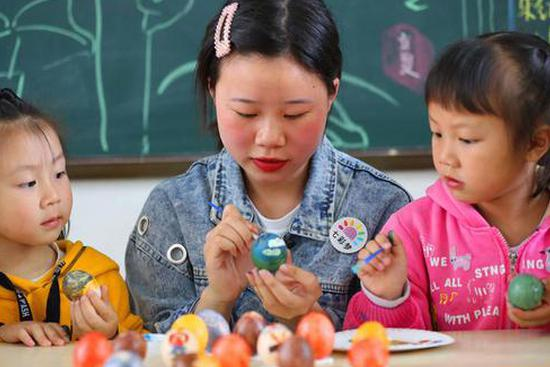 Children paint on eggs under the guide of a teacher to mark the upcoming