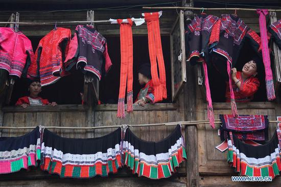 "Women of Yao ethnic group present and dry folk costumes in Longji Township of Longsheng County, south China's Guangxi Zhuang Autonomous Region, July 8, 2018. Local people of Yao ethnic group on Monday celebrated annual ""drying clothes"" festival, which falls on the 6th day of the 6th month of the Chinese traditional lunar calendar. (Photo by Huang Yongdan/Xinhua)"