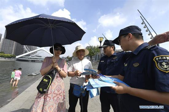 Law enforcement members (1st and 2nd R) from the maritime safety administrations of Tianjin distribute brochures about the Maritime Day of China to citizens in north China's Tianjin, July 11, 2019. The Maritime Day of China falls on July 11 every year. (Xinhua/Yue Yuewei)