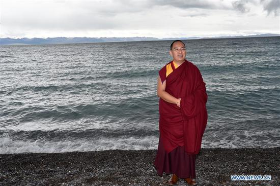 The 11th Panchen Lama Bainqen Erdini Qoigyijabu, also vice president of the Buddhist Association of China, poses for a photo on the bank of Nam Co Lake in southwest China's Tibet Autonomous Region, Aug. 7, 2019. (Xinhua/Chogo)