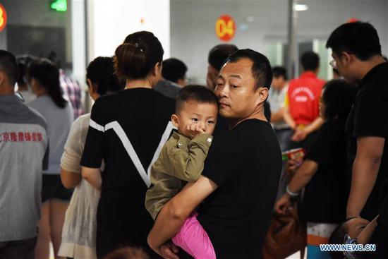 People wait to get meals at a relocation site, in Shouguang, east China's Shandong Province, Aug. 12, 2019. About 93,000 local residents have been relocated as Typhoon Lekima wreaked havoc in parts of Shouguang. (Xinhua/Wang Kai)