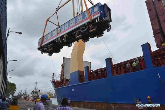 Workers unload one of the carriages of an imported Chinese-made train at Colombo port in Sri Lanka, Aug. 13, 2019. Sri Lanka has imported a train from China for its upcountry line at a cost of 10.3 million U.S. dollar which will be the first of nine power sets, the island's Transport Ministry said in a statement here Tuesday. Quoted in the local media, the Transport Ministry said the train is able to run on winding roads on the upcountry line. (Photo by Gayan Sameera/Xinhua)