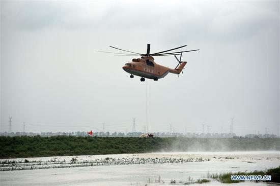 A helicopter airlifts relief materials at the scene of a breached dike of the Mihe River in Shouguang, east China's Shandong Province, Aug. 14, 2019. Rescuers are trying to repair dike breaches triggered by heavy floods brought by typhoon Lekima in Shouguang. (Xinhua/Wang Kai)