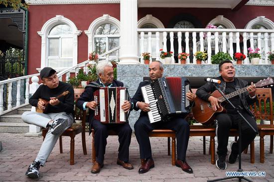 Local residents play musical instruments while attending a feast with neighbors in Tacheng, northwest China's Xinjiang Uygur Autonomous Region, Sept. 4, 2019. (Xinhua/Sadat)