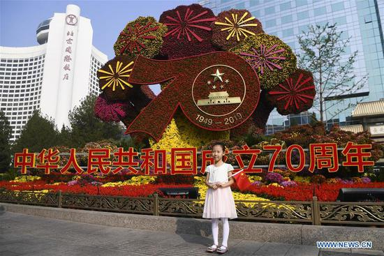 A girl poses for a photo in front of a flowerbed titled