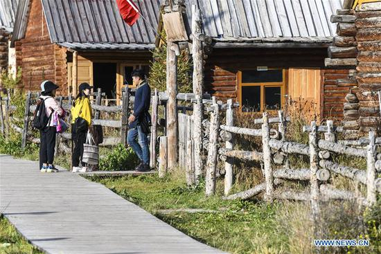 Tourists talk with a man of a homestay at kanas scenic spot in Altay, northwest China's Xinjiang Uygur Autonomous Region, Sept. 25, 2019. More and more tourists choose to experience homestay with strong local characteristic in Xinjiang. (Xinhua/Wang Fei)