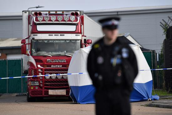 In this photo taken on October 23, 2019, a police officer secures the cordon at the scene where a lorry, found to be containing 39 dead bodies, was discovered at Waterglade Industrial Park in Grays, east of London. [Photo: AFP/Ben Stansall]